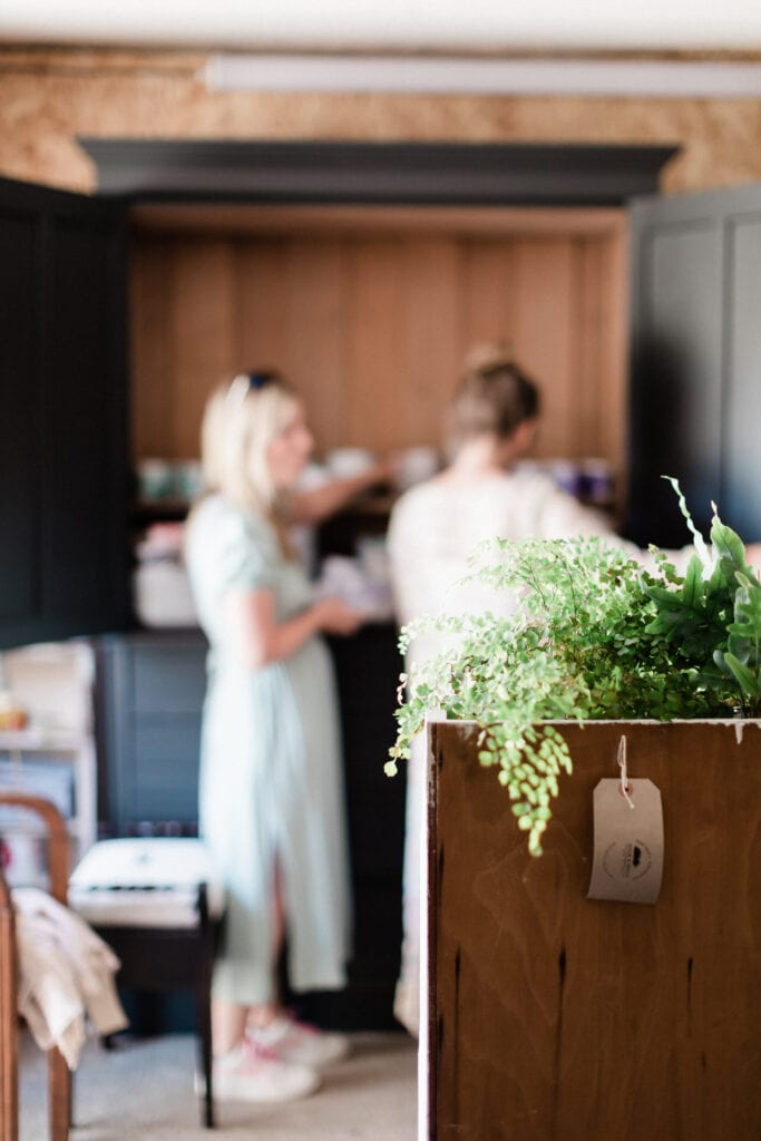 two women in out of focus picture in front of grey cupboard linen press with plants
