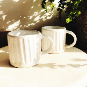 Handmade white glazed pottery mug with indented stripes