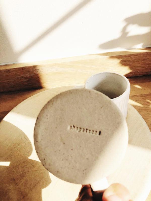 Handmade white glazed pottery mug with indented stripes